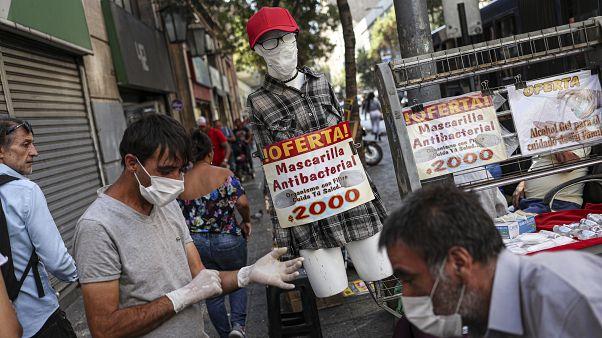 بائع متجول في العاصمة الشيلية سانتياغو يبيع قفازات وأقنعة ومادة الكحول اللزجة للوقاية من فيروس كوفيد-19