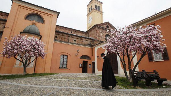 Egy pap sétál maszkban az olaszországi Codognóban