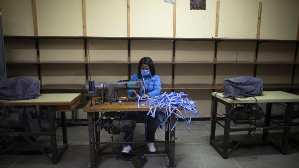 امرأة تخيط أقنعة للوجه خاصة بالفرق الطبية في كاراكاس