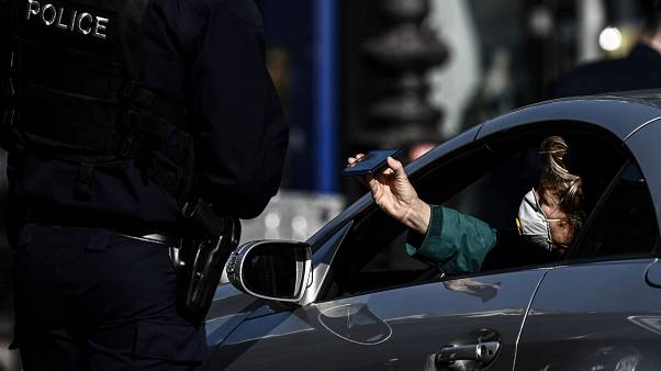 A police officer controls a man in Paris on March 19, 2020. (Photo by PHILIPPE LOPEZ / AFP)