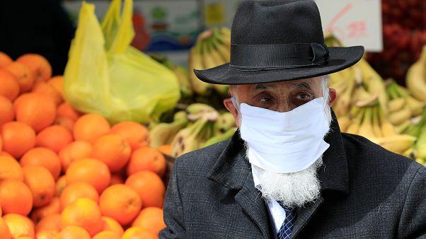 رجل يهودي متدين يضع كمامة ويسير بسوف محانيه يهودا بالقدس الغربية. 19/03/2020