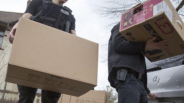 عنصران من الشرطة الألمانية ينقلان علبتين بعد مداهمة أحد البيوت التي كان يستخدمها التنظيم المتطرف