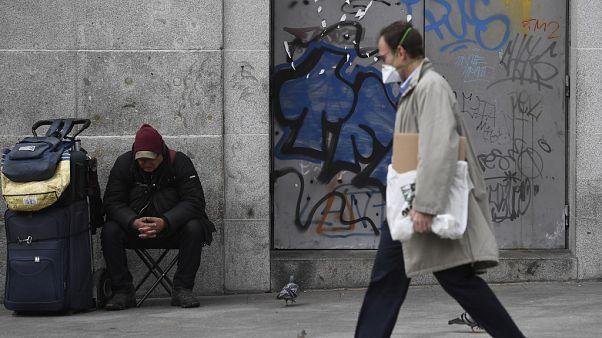 Un hombre protegido con una máscara pasea cerca de un 'sin techo' en Puerta del Sol, Madrid