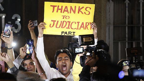 مردی در برابر زندان محل اعدام چهار محکوم هندی، پلاکارتی با مضمون «تشکر از اجرای عدالت» در درست دارد