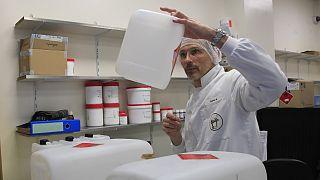 داروساز فرانسوی ظرف حاوی ژل ضدعفونیکننده را بررسی میکند. پاریس مارس ۲۰۲۰
