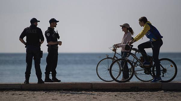 French police issue a warning to cyclists on a beach in Marseille, southern France, Thursday, March 19, 2020.