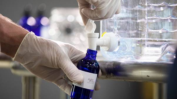 A worker bottles hand sanitizer made at the Eight Oaks Farm Distillery in the USA