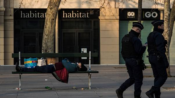 Policemen walks by a homeless man sleeping on a bench on March 17, 2020 in Paris