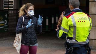 Una mujer habla con un policía en Barcelona, España, el miércoles 18 de marzo de 2020.