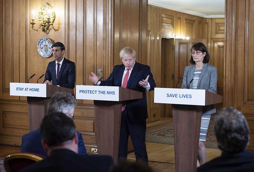 El Primer Ministro británico Boris Johnson, en el centro, el Canciller Rishi Sunak, a la izquierda, y la Subdirectora Médica de Inglaterra, Jenny Harries, participan en la rueda de prensa sobre el Coronavirus en Londres, el 20 de marzo de 2020.