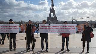 People gather with banners at Trocadero square in Paris, Tuesday, Feb. 11, 2020, calling for the release of French scientists Fariba Adelkhah et Roland Marchal.