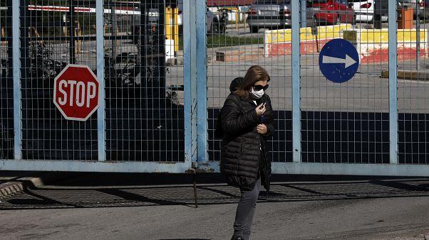 صورة من الأرشيف- امرأة ترتدي كمامة أمام مستشفى أتيكو في أثينا، اليونان
