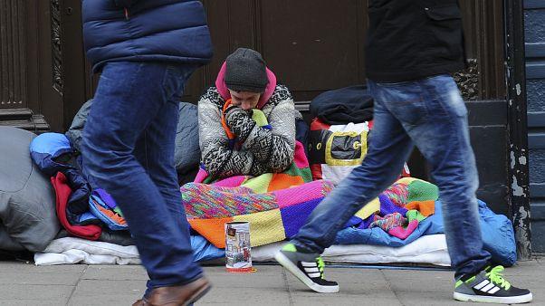 Pedestrians walk past a homeless man in the UK.