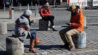 People sit on the bollards on the Admiral Bridge in Berlin's Kreuzberg district on March 22, 2020, amidst the new coronavirus COVID-19 pandemic. (Photo by David GANNON / AFP)
