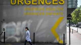 A doctor walks past the entrance of the emergency service of the University Hospital (CHU) in Nantes, western France on April 30, 2019
