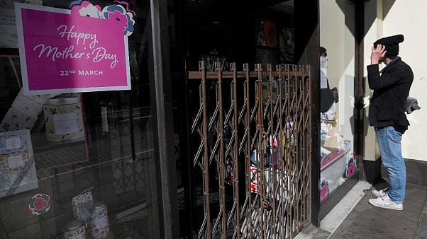 A man looks into a closed shop selling Mother's day gifts in London, Sunday, March 22, 2020.