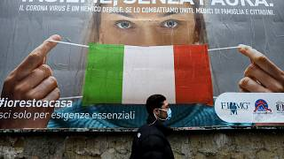A man walks past a large billboard raising awareness to the measures taken by the Italian government to fight against the spread of the COVID-19.