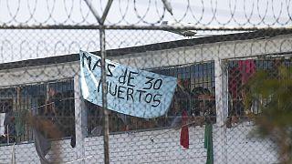 """Los reclusos muestran un cartel que dice """"Más de 30 muertos"""" en la cárcel La Modelo de Bogotá, Colombia."""