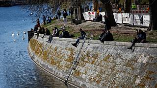 People sit in the sun on the banks of the Landwehr Canal in Berlin's Kreuzberg district on March 22, 2020,