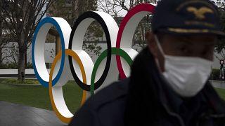 مواطن ياباني يقف امام شعار الالعاب الأولمبية في طوكيو - 2020/03/23