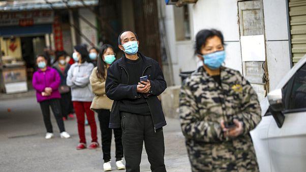 صينيون يصطفون على مسافات متباعدة أمام محل تجاري للتبضع في أحد الأحياء في ووهان الصينية