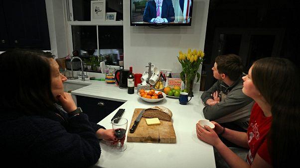 Una familia escucha el discurso televisado del primer ministro Boris Johnson