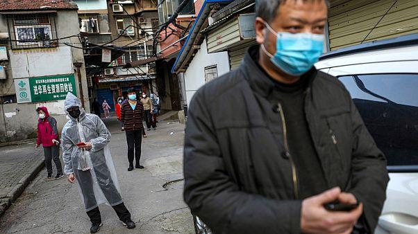 Des habitants font la queue pour acheter du porc à l'entrée de leur résidence, le 18 mars à Wuhan en Chine