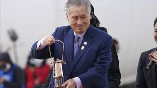 In this March 20, 2020, file photo, Japanese comedians Mikio Date, foreground, and Takeshi Tomizawa leave with the Olympic flame in northern Japan.