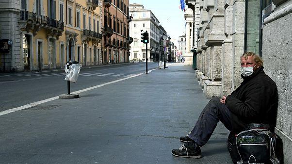 Un 'sin techo' en Via del Corso en Roma