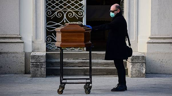 A man touches the coffin of his mother during a funeral service in the closed cemetery of Seriate, near Bergamo