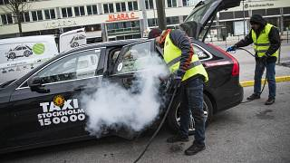 رجلان يعقمان سيارة أجرة بالعاصمة السويدية ستوكهولم منعا لانتاشر فيروس كورونا. 24/03/2020