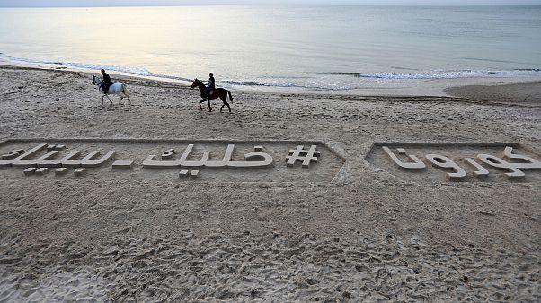 شعار رملي على طول شاطئ في مدينة غزة يدعو الناس إلى البقاء في البيوت