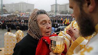 Eine Frau empfängt die Kommunion in Bukarest, 2018.