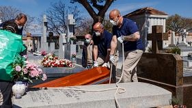The coffin of a COVID-19 coronavirus victim is buried at Fuencarral cemetery in Madrid on March 29, 2020.