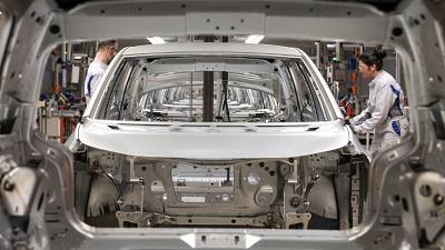 Workers complete an electric car ID.3 body at the assembly line during a press tour at the plant of the German manufacturer Volkswagen AG .