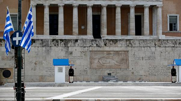 Municipal workers install Greek flags in front of the Greek parliament as Presidential guards are on duty at the empty Tomb of the Unknown Soldier Athens on March 24, 2020.