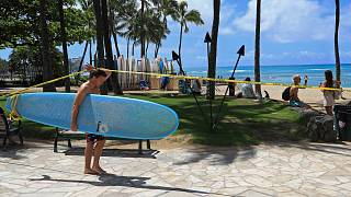 Un surfeur passe sous la ligne de signalisation à Waikiki, le vendredi 20 mars 2020, à Honolulu.