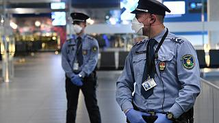 Hungarian police officers wearing protective face masks stand on guard in the hall of Budapest's Liszt Ferenc Airport of on February 5, 2020