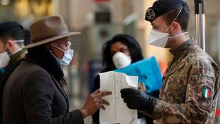 A soldier checks a passenger's papers at Milan's main train station, Italy