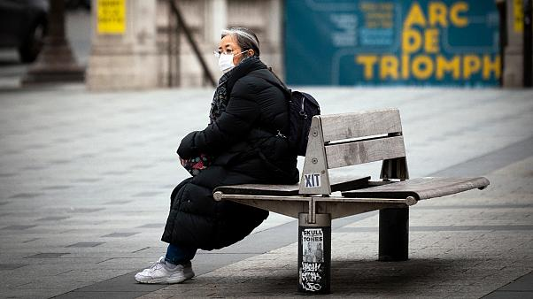 A  woman wearing a face mask sits on a bench on the Champs-Elysees avenue in Paris, on March 16, 2020.