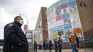 ABD New York'ta aralarına mesafe koyarak bekleyen halk ve maskeli görevli bir polis memuru.