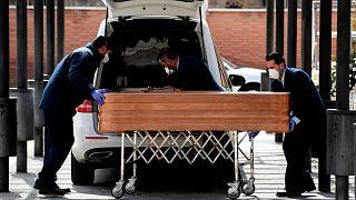 Le cercueil d'une victime du Covid-19 pris en charge par des agents funéraires, dans un cimetière de Madrid le 24 mars 2020.