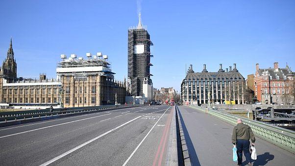 Un piéton traverse le pont de Westminster dans le centre de Londres vidé de ses habitants, le 24 mars 2020
