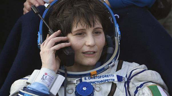 Italian astronaut Samantha Cristoforetti speaks on a satellite phone outside of the Soyuz AFP PHOTO / POOL / IVAN SEKRETAREV (Photo by IVAN SEKRETAREV / POOL / AFP)