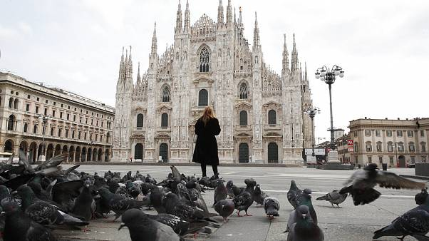 A woman stands in front of the Duomo cathedral, in downtown Milan, Italy.