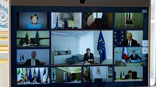 Members of the European Council are seen on the screen during a video conference call at the Elysee Palace in Paris, Thursday March, 26 2020.