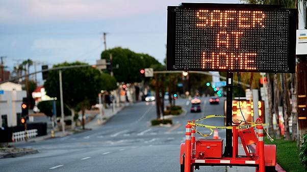"""Panneau de signalisation routière recommandant indiquant """"Plus en sécurité à la Maison"""" déployé dans les rues de Monterey Park en Californie, le 25 mars 2020."""