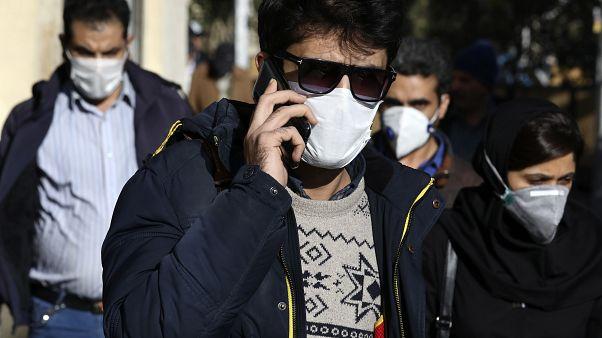 Un homme portant un masque de protection contre le nouveau coronavirus, parle sur son téléphone portable dans le centre de Téhéran, en Iran