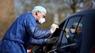 German doctor Michael Grosse swabs the throat of a car driver through the window on March 27, 2020 at a drive through testing point in Halle, eastern Germany.