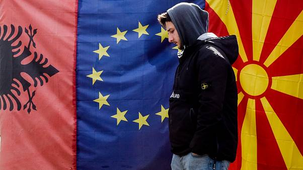 A man walks by Albanian EU and North Macedonia flags displayed in a bazaar in Skopje, on February 6, 2020.
